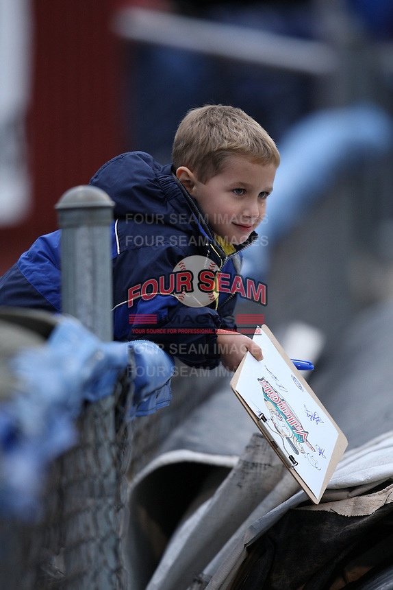 A Tri-City Valleycats young fan braves the cold rainy weather to get some autographs before game two of the NYPL Semifinals vs. the Batavia Muckdogs at Dwyer Stadium in Batavia, New York September 8, 2010.   Batavia defeated Tri-City 5-4.  Photo By Mike Janes/Four Seam Images