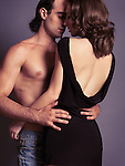Sensual portrait of a young sexy couple about to kiss. Man with bare torso embracing a woman in dress with open low back. Isolated on gray background.