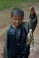 CAMBODIA 2007, BENG MEALEA TEMPLE, BOY IN POURING RAIN WITH FISH AND FROGS, during the Monsoon season in Cambodia
