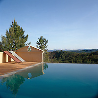 A pair of sunloungers is propped against the wall of this inifinity pool overlooking the surrounding countryside