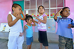 In Zapotal, Mexico, 3-year old Luz Elena Martinez (second from left) goes to preschool one hour a day to help prepare her to go full time the following year. In this image, the girl, who is blind, is getting help from her older sister, 5-year old Sandra, during a game. Sandra will graduate from preschool the coming year, but before that she's getting Luz accustomed to the school environment to make for an easier transition.