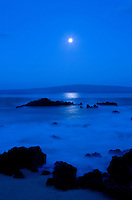 The full moon shines on the misty ocean at Makena on Maui, with Kaho'olawe in the distance.