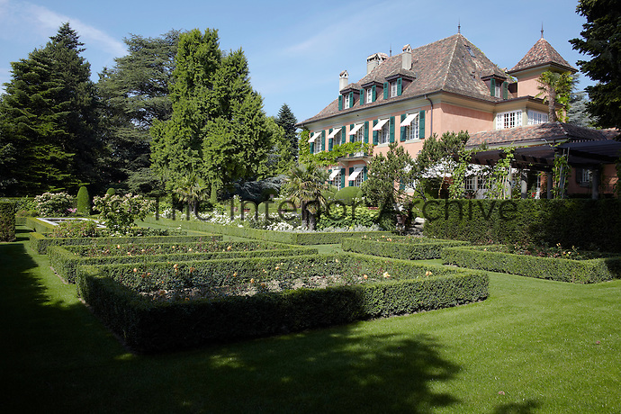 The sweeping lawns of the manicured garden are punctuated with beds of roses framed with trimmed box hedges
