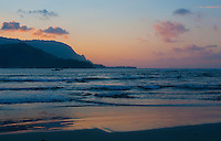 A rosy pink glow lights up the sunset sky and water's edge at Hanalei Beach Park and Na Pali on the North Shore of Kauai.