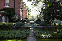 A flagstone path leads from the garden down the side of the house to a raised stone terrace