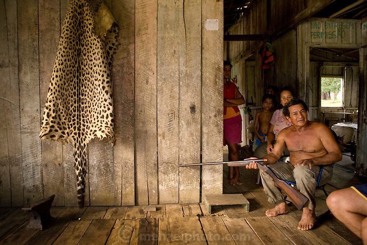 Rancher Francisco Da Silva Correia holds a shotgun and recounts the story of how he killed the jaguar, whose skin is on the wall, in his riverside home near the town of Caviana, Amazonas, Brazil.