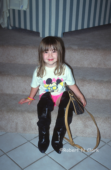 Girl wearing her mother's patent leather boots and holding her purse