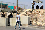 A Palestinian man walks in front of Israeli border guard at a newly erected checkpoint in Jerusalem's neighborhood of Jabal al-Mokaber on October 19, 2015. Israeli police began erecting a wall in east Jerusalem to protect a Jewish neighbourhood subject to firebomb and stone attacks launched from an adjacent Palestinian village. Photo by Mahfouz Abu Turk