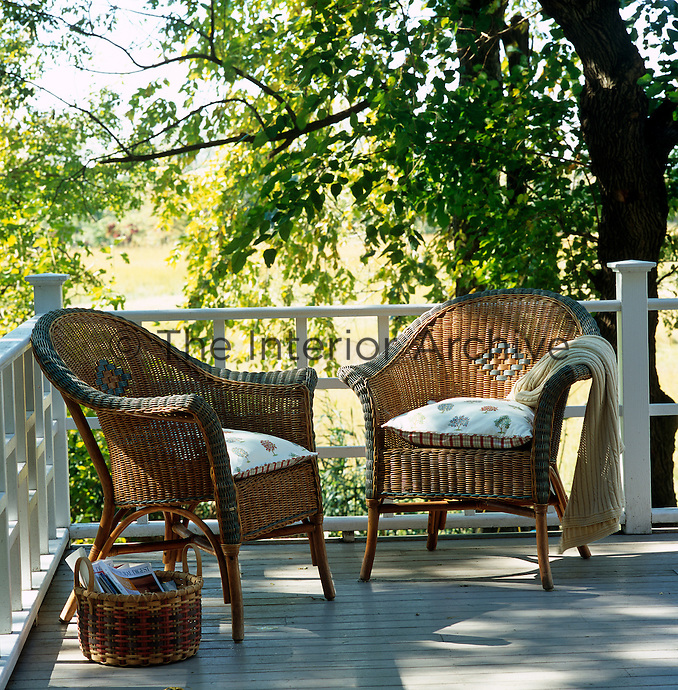 A pair of wicker armchairs in the shade of a tree on a peaceful terrace