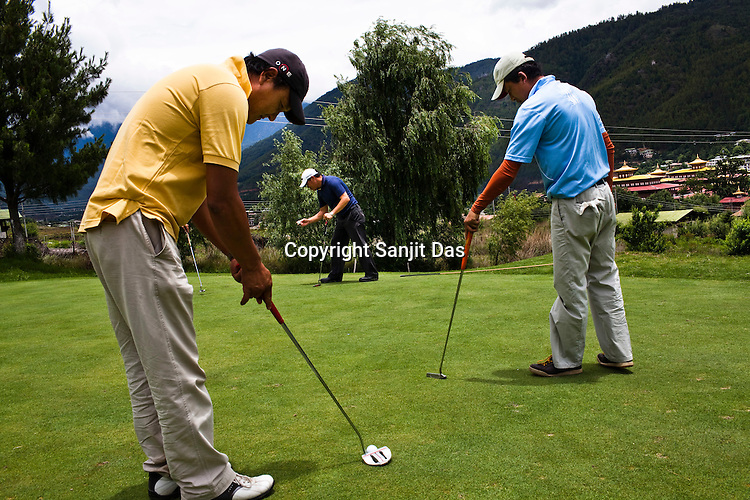45 year old, Samdrup Norbu (in yellow) putts the ball on the greens at the Royal Thimphu Golf Course in Thimphu, Bhutan. Photo: Sanjit Das/Panos
