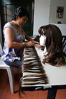 A woman works with wigs for cancer patients before being donated as a commitment to actively fight against cancer in Medellin, Colombia, May 25, 2012.  Colombia celebrated on 31 January, 7, 14 and 21 February some days of donating hair in Beauty Centres Fundayama ALQVIMIA and foundation (Foundation for support and support people with breast cancer), it received 300 donations of hair with which they made 200 wigs  Photo by Fredy Amariles/View