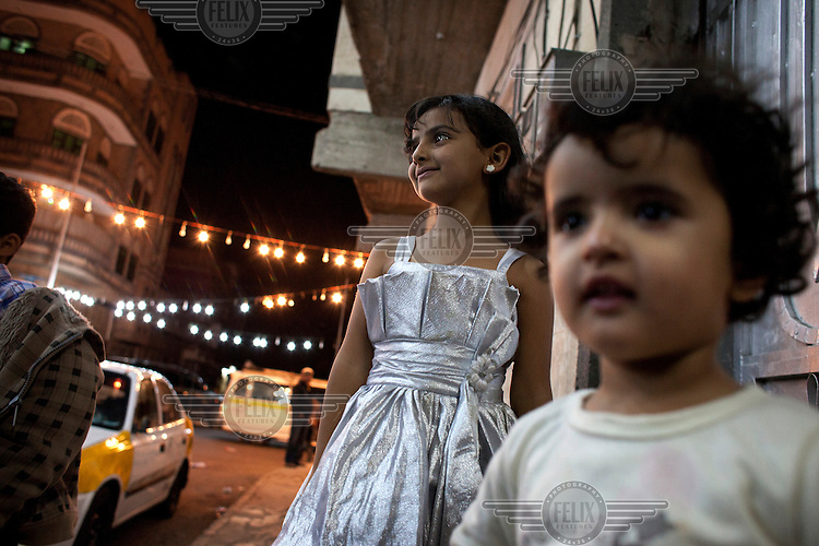 Young girls stand out on the street awaiting the bride to arrive home from the wedding.