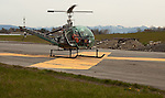 A Hiller helicopter lands on a large yellow X painted on the runway.