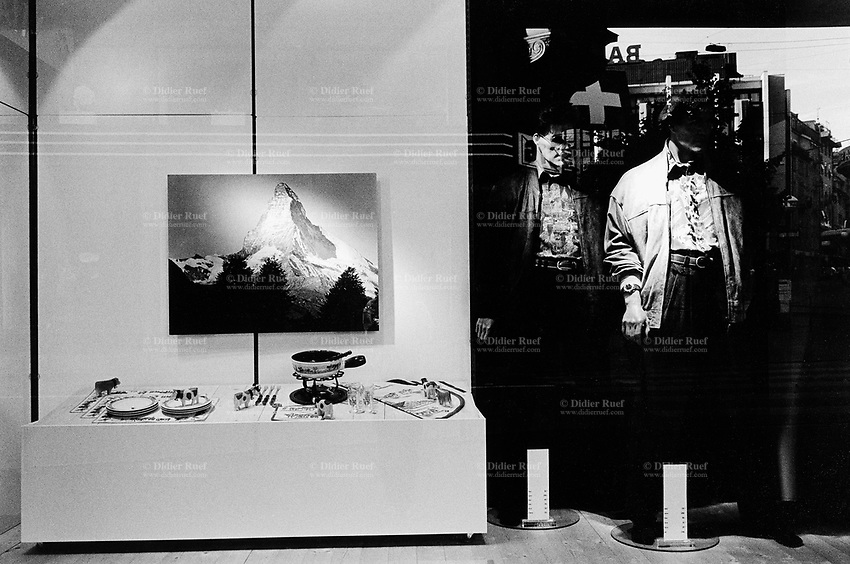 Switzerland. Zürich. On display at a shop's window, a picture from the Matterhorn mountain, a set of plates and pot for the cheese fondue, two mannequins with men's fashionable clothes, and a swiss flag. Fondue is a Swiss dish of melted cheese served in a communal pot (caquelon or fondue pot) over a portable stove (réchaud) heated with a candle or spirit lamp, and eaten by dipping bread into the cheese using long-stemmed forks. It was promoted as a Swiss national dish by the Swiss Cheese Union (Schweizerische Käseunion) in the 1930s. The Matterhorn (French: Mont Cervin) is a mountain of the Alps, straddling the main watershed and border between Switzerland and Italy. It is a large, near-symmetrical pyramidal peak in the extended Monte Rosa area of the Pennine Alps, whose summit is 4,478 metres  high, making it one of the highest summits in the Alps. The flag of Switzerland displays a white cross in the centre of a square red field. The white cross is known as the Swiss cross. © 1990 Didier Ruef