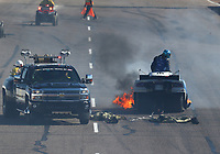 Feb 24, 2018; Chandler, AZ, USA; The NHRA Safety Safari tends to funny car driver Tommy Johnson Jr as he climbs from the emergency roof escape hatch after suffering an engine explosion and fire during qualifying for the Arizona Nationals at Wild Horse Pass Motorsports Park. Johnson would be uninjured in the incident. Mandatory Credit: Mark J. Rebilas-USA TODAY Sports