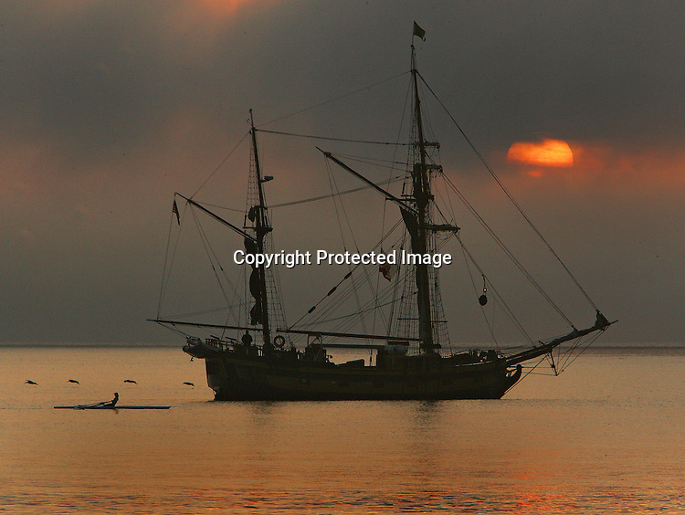 A rower exercises past our clipper ship in Sausalito harbor during sunrise on San Francisco Bay, California