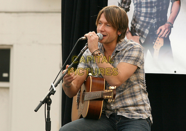 KEITH URBAN.is joined by Verizon Wireless and Samsung Mobile as he makes an in-store appearance for his fans at the Verizon Wireless store in Pasadena, California, USA, November 21st 2009                                                                   .half length music concert gig live on stage grey gray brown plaid checked check shirt microphone tattoo bracelets singing  sitting jeans guitar .CAP/RKE/DVS.©DVS/RockinExposures/Capital Pictures