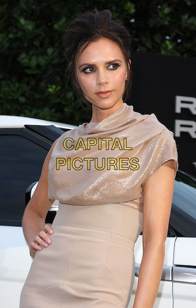 VICTORIA BECKHAM .(wearing Victoria Beckham dress).Attends the Range Rover 40th Anniversary Party in association with Vogue at the Orangery, Kensington Palace, London, England, Uk, .July 1st 2010..half length beige gold shimmery shiny sparkly ruched top high waisted waist skirt asymmetric hand on hip nude.CAP/ROS.©Steve Ross/Capital Pictures.