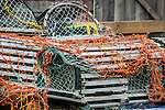 A pile of wooden lobster traps with colorful netting on a dock at Peggy's Cove, Nova Scotia