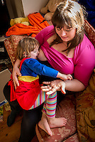 """A woman  7 months pregnant breastfeeds her little girl aged nearly 3 years old on the sofa in her living room. They are playing the  Incy Wincy Spider song/game at the same time.<br /> <br /> Image from the """"We Do It In Public"""" documentary photography project collection: <br />  www.breastfeedinginpublic.co.uk<br /> <br /> Dorset, England, UK<br /> 14/02/2013"""