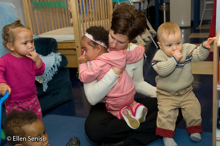MR / Schenectady, NY.Schenectady Day Nursery / private non-profit daycare center / Infant Class.Teacher comforts baby girl  (1, African-American / Caucasian) crying after her mother dropped her off at daycare..MR: Kin6, Far3 .© Ellen B. Senisi