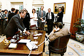 "White House Chief of Staff James A. Baker, III offers a victory glass of champagne to United States President Ronald Reagan as he talks to the Speaker of the House Thomas P. ""Tip"" O'Neill over the phone in the Oval Office of the White House on Wednesday, July 29, 1981.  Staff members Karna Small, David Gergen, Edwin Meese and Vice President George H.W. Bush look on..Mandatory Credit: Michael Evans - White House via CNP"