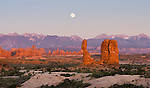 Panoramic image of a full moonrise over the La Sal Mountains and Balanced Rock in Arches National Park, Moab, Utah, USA at sunset with cloudless skies.