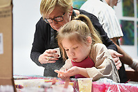 """Alisa McWhirt of Rogers (left) helps Cadence McWhirt, 5, of Bentonville (center) blow glitter on an art piece, Sunday, February 9, 2020 at Heart & Soul Studios NWA in Rogers. Check out nwaonline.com/200210Daily/ for today's photo gallery.<br /> (NWA Democrat-Gazette/Charlie Kaijo)<br /> <br /> The studio held their first """"Bring Your Grandparents to Paint Day"""" event. Marie Haley, owner of the studio, wanted to create an opportunity for grandparents and their grand kids to spend some time together to do something creative and unique. """"They're painting themselves. Usually grownups just come and watch,"""" said Haley. The next event will be in March and they plan to hold the event each month moving forward."""