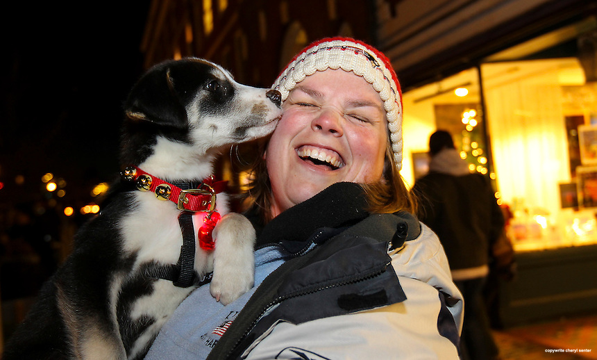 Tina Favara of Kensington gets a lick from her newly adopted rescue puppy, Timber, while waiting for the start of the Portsmouth Illuminated Holiday Parade and Tree Lighting event in Portsmouth, N.H., Saturday, Dec. 7, 2013.  (Portsmouth Herald Photo Cheryl Senter)