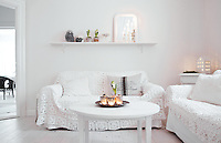 White, silver and grey shades combine in the living room where the glow from lit candles creates a cosy atmosphere