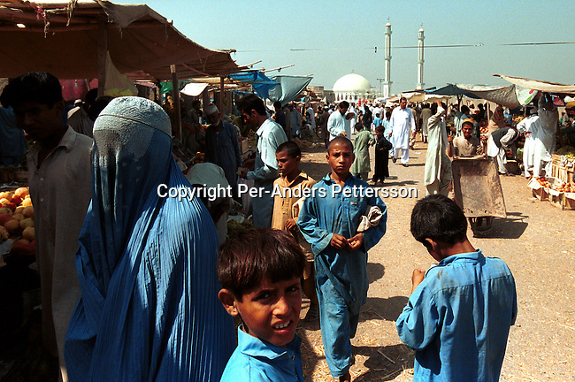 An Afghan refugee women dressed in a traditional Burqa in a market on October 3, 2001 in Peshawar Pakistan. The women have to wear a traditional Burqa dress while walking in the streets. About 1 million Afghan refugees are in Pakistan, mainly in Peshawar. .(Photo Per-Anders Pettersson/ Grazia Neri