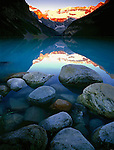 Banff National Park, Canada    <br /> Sunrise lights Mount Victoria and Victoria Glacier with reflections on Lake Louise and shoreline boulders