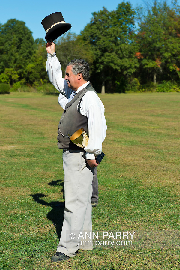 Old Bethpage, New York, U.S. 29th September 2013.  Referee GARY MONTI, of Westbury, holding a trophy cup, tips his top hat to the teams after the Old Time Base Ball championship game, where Brooklyn Eckfords beat Brooklyn Excelsiors, at The Long Island Fair. A yearly event since 1842, the county fair is now held at a reconstructed fairground at Old Bethpage Village Restoration.