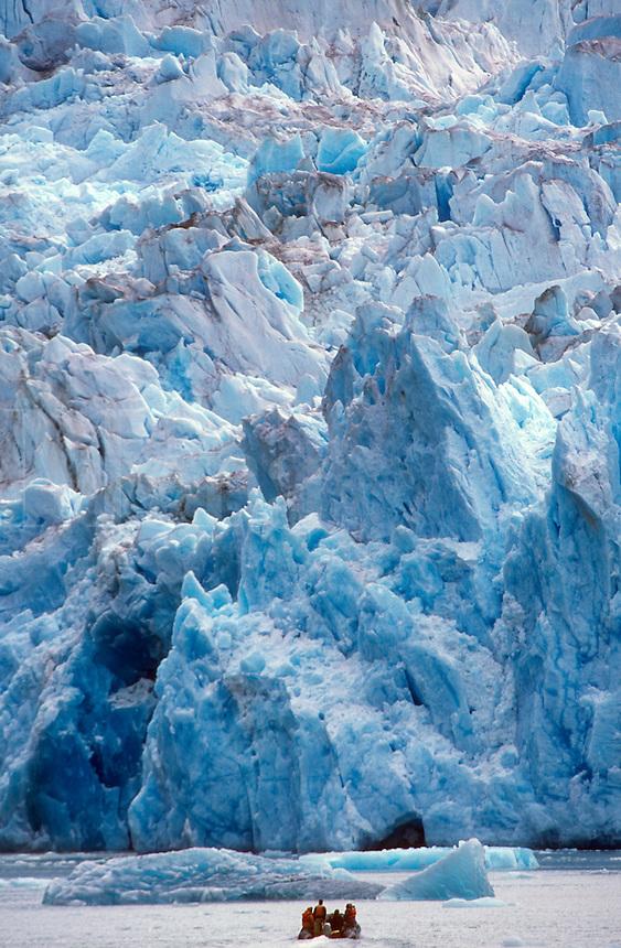 Vacation adventurers approach the face of South Sawyer Glacier a motorized skiff (Zodiak).