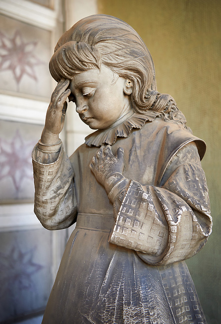 Picture and image  of the Realistic young grieving girl stone funary monument sculpture  commissioned by Enrico Amerigo for his sisters memory. beside the pedestal on which the sculptor set the deceased's bust he placed, on the left, the figure of an old blind man, kneeling down and leaning on a stick; on the right he placed the figure of a young orphan girl, recognizable as such by her kindergarten uniform, portrayed in the act of making the sign of the cross. This work belongs to the Realism, a trend which was typical during the 1880s and 1890s, according to which the orphans, the poor, the sick and all those who benefited from somebody's generosity had to be portrayed in a concrete fashion. Sculptor G Moreno 1890. Section A, no 53, The Staglieno Monumental Cemetery, Genoa, Italy