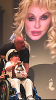"""Pictured: Seth Burke on stage speaking via video link to Dolly Parton<br /> Re: A brave schoolboy had his wish come true when he sang a duet with his favourite signing star Dolly Parton.  <br /> Seth Burke, nine, always listens to Queen of Country Dolly when he's in hospital having treatment for Duchenne's muscular dystrophy.<br /> Doting parents Lisa and John took him on a Caribbean cruise where the crew heard about his love for Dolly. <br /> The family was called up on stage one night and heard a familiar Tennessee drawl say: """"Hi Seth!""""<br /> The schoolboy couldn't believe his eyes when he turned to see Dolly on a huge TV screen.<br /> Seth, of Grangetown, Cardiff, was diagnosed with Duchenne Muscular Dystrophy when he was a baby."""