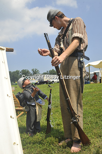5-year-old Bryan Holtzer looks up to David Ferencuzy as Ferencuzy teaches him about loading a Civil War era firearm at the Civil War encampment at the Fauquier County Fair. --Staff Photo/Randy Litzinger