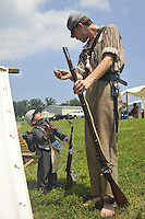 5-year-old Bryan Holtzer looks up to David Ferencuzy as Ferencuzy teaches him about loading a Civil War era firearm at the Civil War encampment at the Fauquier County Fair.