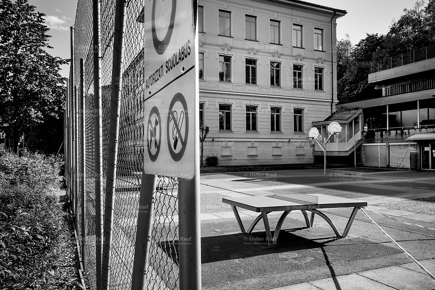 """Switzerland. Canton Ticino. Lugano. Police line. The schools are closed. Nobody can enter the courtyard  Due to the spread of the coronavirus (also called Covid-19), the Federal Council has categorised the situation in the country as """"extraordinary"""". It has issued a recommendation to all citizens to stay at home, especially the sick and the elderly. From March 16 the government ramped up its response to the widening pandemic, ordering the closure of bars, restaurants, sports facilities and cultural spaces. Only businesses providing essential goods to the population – such as grocery stores, bakeries and pharmacies – are to remain open. 29.04.2020 © 2020 Didier Ruef"""