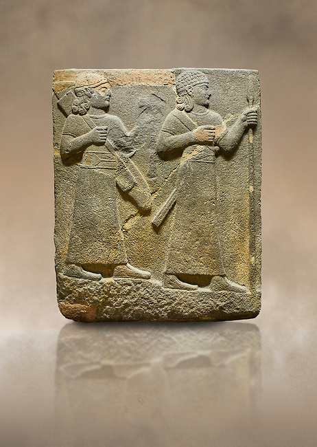 Photo of Hittite relief sculpted orthostat stone panel of Royal Buttress. Basalt, Karkamıs, (Kargamıs), Carchemish (Karkemish), 900-700 B C. Warriors. Anatolian Civilisations Museum, Ankara, Turkey.<br /> <br /> Two figures are seen, each with a long dress, a thick belt and curled hair. The figure in front carries a spear in his left hand and a long sword at his waist, and the figure behind carries an axe in his left hand and a quiver on his back.   <br /> <br /> Against a brown art background.