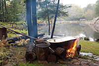 In a tranquil spot beside the lake a roll top bath is balanced on logs over an open fire while the water is heated
