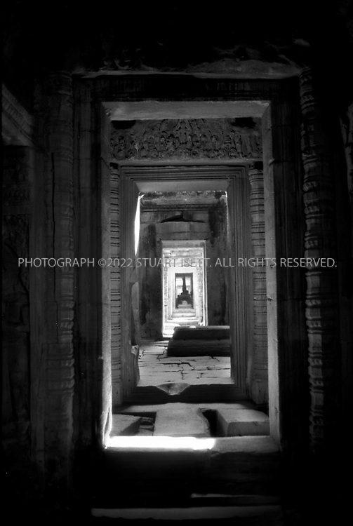 4/20/2003--Angkor Wat Temples, Siem Reap, Cambodia..PRAH KHAN.The sacred sword ..Prah Khan, the Beguiler, the Romancer, and the artist. It was built in second half of the 12th century (1191) by king Jayavarman VII, dedicated to the father of the king (Buddhist), with following to Prasat Bayon art style...Four causeways lead to the temple and are bordered by the same figures (giants and gods carrying a serpent as are found at the entrances to the city of Angkor Thom (not shown on the plan). This architectural element was the mark of a royal city. The absence of towers with faces such as those found at other temples built by the same king suggests Prah Khan is earlier. It may have served as a temporary residence of King Jayavarman VII while he was rebuilding the capital after the Chams sacked it in 1177. ..Prah Khan shares similarities with the temple of  Ta Prohm. The main elements are contained in a small space giving a cramped feeling. Much of the temple is in poor condition but even restored it would seem architecturally complex. ..An inscription found in 1939 indicates Prah Khan was the ancient city of Nagarajayacri. the second part of the name, Jayacri , is the Thai word for sacred sword, the meaning of Prah Khan. The sacred sword has a long history in Khmer tradition as in the late in the century Jayavarman II left his successor a sacred sword, the Prah Khan , which descendants still guard. Coeds, though, suggests that the legend of the sacred sword may have originate with the Thais who still call their sacred sword  ' Jayacri '...Photograph by Stuart Isett.©2003 Stuart Isett