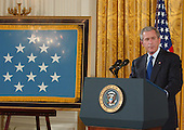 Washington, D.C. - April 4, 2005 -- United States President George W. Bush makes remarks prior to presenting the nation's highest award for valor, the Medal of Honor, posthumously awarded to Sergeant First Class Paul Ray Smith, United States Army, in the East Room of the White House in Washington, D.C. on April 4, 2005. Sergeant Smith was killed on April 4, 2003 while protecting over one hundred troops under his command near Baghdad Airport.  Smith is the first soldier from Operation Iraqi Freedom to be awarded the Medal of Honor.  The flag on the easel at left is the first to be awarded since its inception by an act of the United States Congress.  To receive the award for Sergeant Smith: Jessica Smith, daughter; Birgit Smith, wife; and David Smith, son, age 11.  <br /> Credit: Ron Sachs / CNP