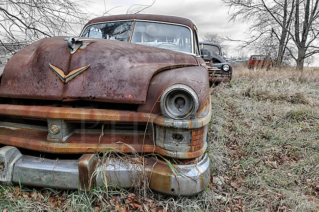 A rusty and abandoned 1950's Chrysler car sitting beat up and weathered in the winter weeds of a rural farm barnyard in Pennsylvania.