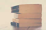 a photograph of a pile of fiction paperback books with a lot of light behind them