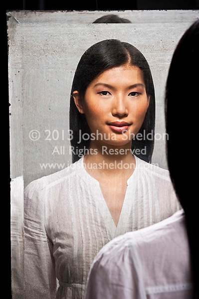 Reflection of young Asian woman in antique mirror