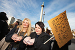 "© Joel Goodman - 07973 332324 . 09/12/2010 . London , UK . Two women with "" Clegg is Tory Scum "" written across both their knuckles and a home made placard reading "" Nick Clegg fuck you . Fuck you for Turning Blue "" in Trafalgar Square . Students and their supporters demonstrate in Parliament Square in London against government cuts to student support , Educational Maintenance Allowance ( EMA ) and rising university tuition fees . Photo credit : Joel Goodman"