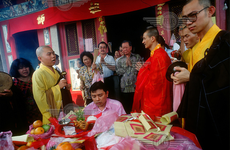 Businessman making offerings and paying for prayers by monks and priests at a Chinese Buddhist temple.
