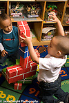 Day Care Center 2-3 year olds two boys working together building with cardboard blocks