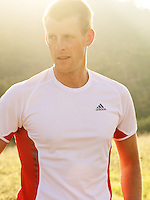 Portrait of a male runner, backlit with lens flare.